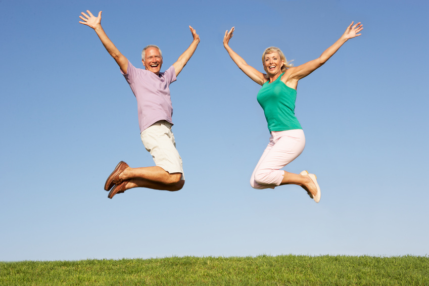 Happy healthy senior couple jumping energetically in air
